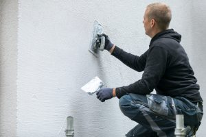 construction worker putting decorative plaster on house exterior