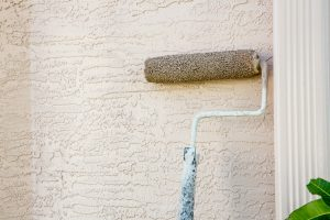 Paint roller attached to pole on outside wall of house