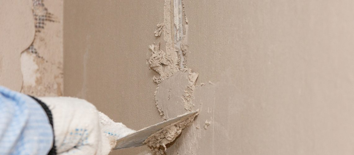 Hand with a spatula in the process of leveling the raw plaster.
